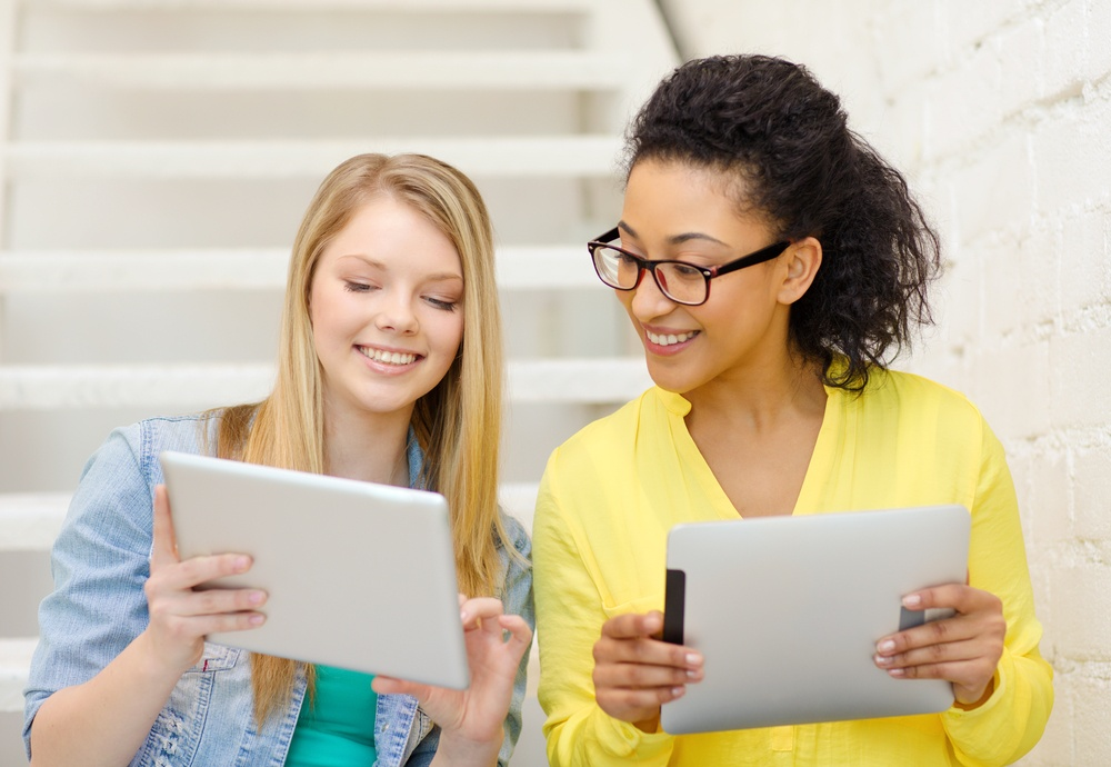 Two women comparing MROC proposals on tablets